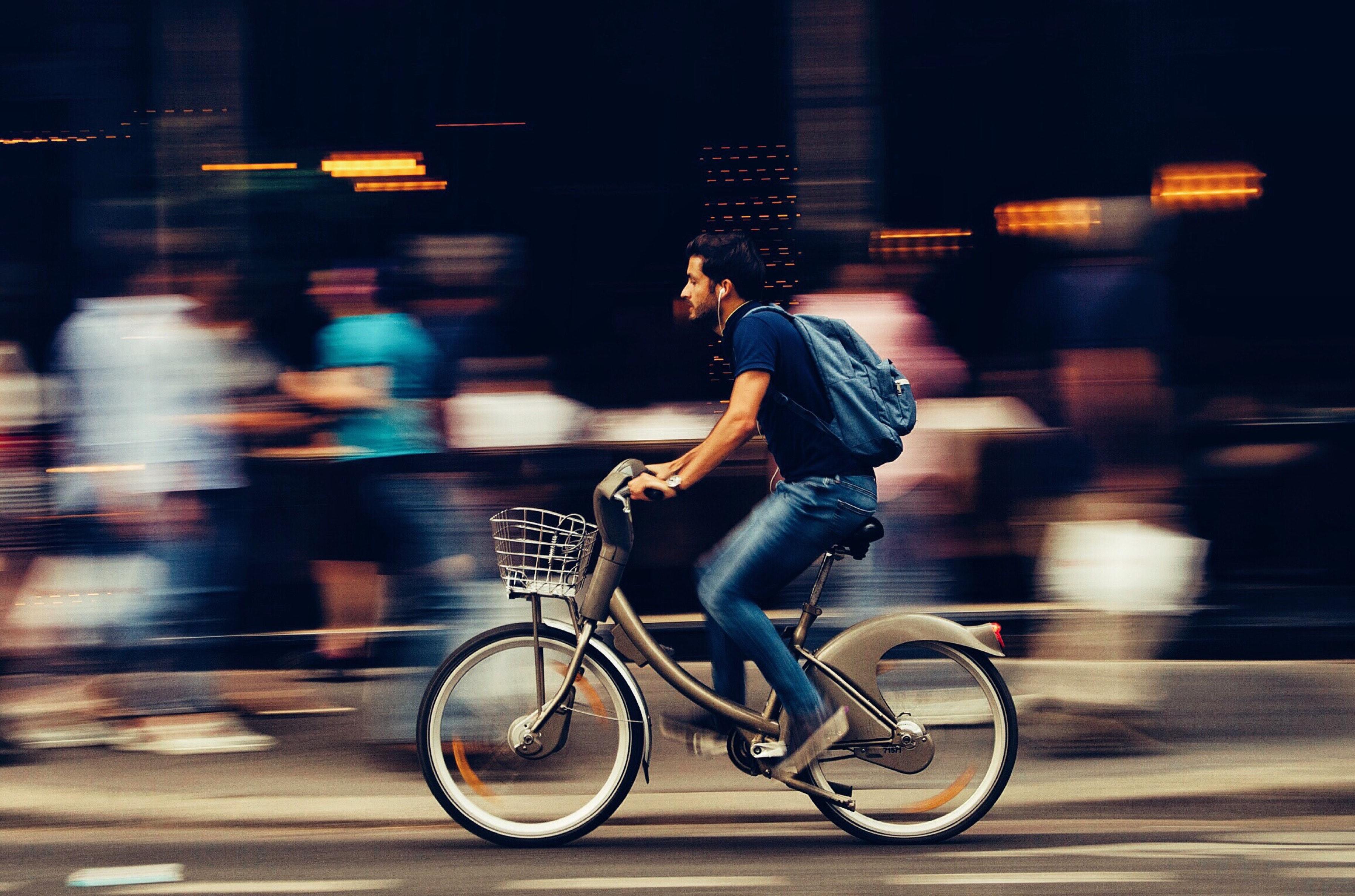 Man som cyklar förbi människor